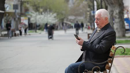 впечатляющий : Profile of a modern old man in his seventies touching the screen and sitting on a bench in a city alley on a sunny day in spring.