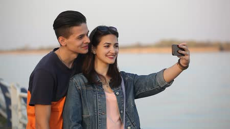 słoneczko : Portrait of a romantic young man kissing his lovely girl on the Dnipro embankment in spring in slow motion. They take a selfie together.