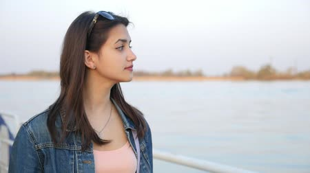 nobreza : Profile of a stylish and romantic young woman strolling along a picturesque Dnipro river embankment on a sunny day in spring in slo-mo Vídeos