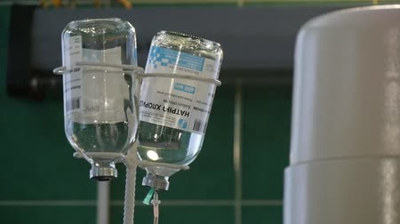 saline drip : An impresssive view of a medical drop counter with two bottles fixed upside down with falling droplets of saline for intravenous infusion