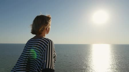темно синий : Back view of a stylish blond woman in a waving striped blouse standing on the Black Sea shore at a golden sunset with a sun path in slow motion