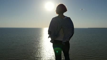 marynarka wojenna : Back view of a romantic blond woman in a waving striped blouse standing on the Black Sea shore at a magic sunset with a sun path in slow motion