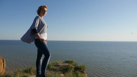 темно синий : Profile of a happy blond woman in a striped navy blouse smiling cheerfully and looking at the Black Sea on a sunny day in summer in slow motion Стоковые видеозаписи