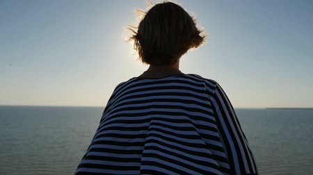 over the shoulder view : back view of a dainty blond woman in a sunglasses standing on the Black Sea  coast at a sparkling sunset with a sun path in slow motion