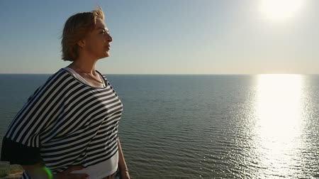 темно синий : Profile of a charming blond woman in a waving blouse smiling happily and looking at the Black Sea at a splendid sunset in summer in slo-mo
