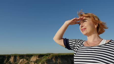 uzakta bakıyor : Profile of a cheery woman in a striped blouse looking away while keeping her hand over the eyes on thehilly  Black Sea coast in summer in slo-mo