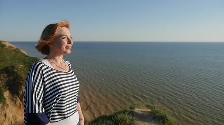 biodro : Profile of a cheery blond woman in a striped navy blouse smiling and looking faraway at the Black Sea on a sunny daay in summer in slow motion