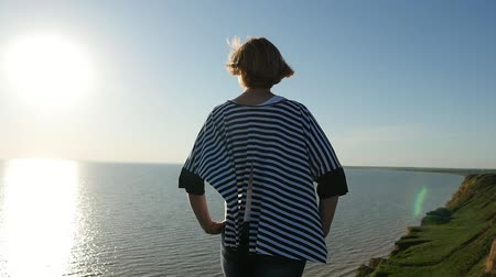 темно синий : Back view of a slender blond woman in a striped sea pareo keeping hands on her hips and looking at a splendid path at sunset in summer in slo-mo