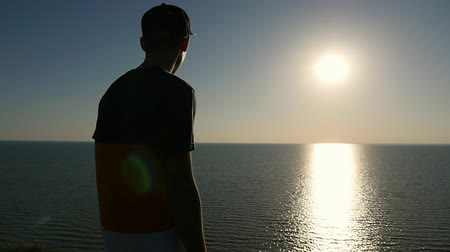 umutlu : Back view of a cheerful man in a striped T-shirt,  cap, and pants standing at the Black Sea and looking at the golden sun path at sunset in slo-mo