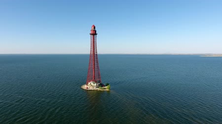 felhőtlen : An exciting bird`s eye view of the high red lighthouse from metallic stripes on the Black Sea shallow on a sunny day in summer. The sky is horizonless