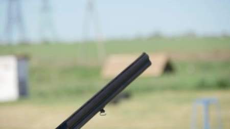 pulling up : Closeup of a hunter keeping his modern double barrel gun, targeting and shooting at clay plates. The recoil rocks the rifle on a range in slo-mo