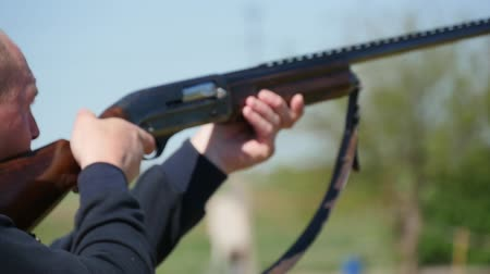 spent : Closeup of a rifleman holding his single barrel rifle, targeting and shooting at clay pigeons. A white cartidge falls down on a range in slo-mo Stock Footage