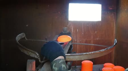 galeria : Closeup of a clay pigeon thrower with a man flinging orange clay targets on a range through a small window in summer in slow motion