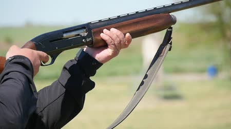 spent : Profile of a pro man holding his single barrel rifle, aiming and shooting. A white cartidge falls down. The recoil jolts the gun in slo-mo Stock Footage