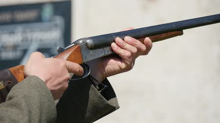 single shot : Closeup of a man with a single barrel rifle aiming, pulling the trigger fast and shooting at a flying clay skeet on a range in summer Stock Footage