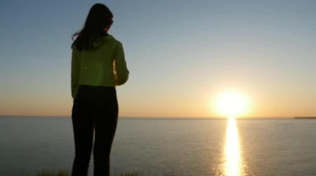słoneczko : Back view of a girl in love with long loose hair standing on the Black Sea shore and thinking about her boyfriend at sunset with a sun path in summer Wideo