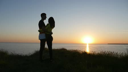 amoroso : A romantic view of an amorous couple embracing each other and enjoying life at sunset with a golden sun path on the Black Sea shore in summer