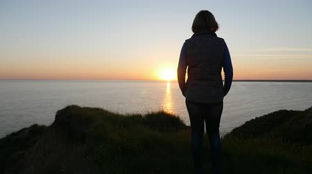 delgado : Back view of a dreaming woman in jeans and a blouse standing on the Black Sea coast and enjoying the view of the golden sun path at sunset in summer
