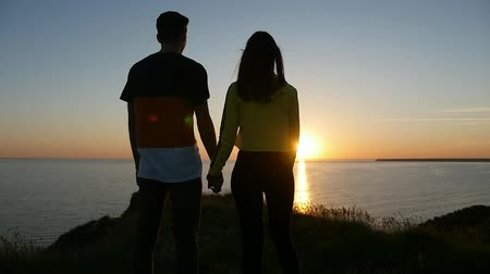 optimistický : An exciting view of a pair in love keeping the hands of each other on the Black Sea coast and looking at sunset with a sun path in summer