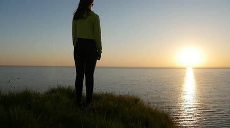 słoneczko : Back view of a nice girl in jeans and a blouse standing on the Black Sea coast and thinking about her Mr.Right at sunset with a sun path in summer