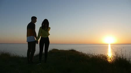 darling : A splendid view of a couple in love keeping the hands of each other and talking on the Black Sea coast at sunset with a sun path in summer Stock Footage