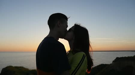 darling : A wonderful view of a pair in love hugging and looking at each other at sunset with a golden sun path on the Black Sea shore in summer