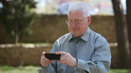 on the phone : An impressive view of a cheery elder man in a grey shirt and necktie smiling and watching some jolly video on his smartphone in a street in summer Stock Footage