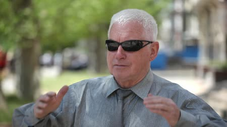 bölcs : Portrait of a white-headed man putting on fashionable sunglasses and putting his short hair in order optimistically in a city park in summer Stock mozgókép