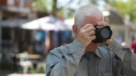 moudrý : An impressive view of a white-headed man with a short haircut in a grey shirt standing in a street, turning his camera shooting pans in summer Dostupné videozáznamy