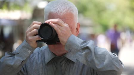 moudrý : A splendid view of a white-headed man with a short haircut in a grey shirt and a necktie standing in a street and taking photos  in summer