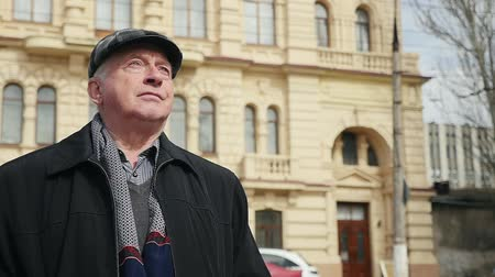 vrásčitý : Profile of a confident senior man in a chechered cap standing in a sunny street with a hictoric building in the background in slo-mo