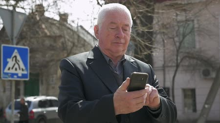 bölcs : A 180 degree shot of an elderly man in a business suit browsing the net on his smartphone in a  sunny street with old houses in slo-mo Stock mozgókép