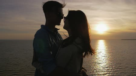 gevşemiş : Profile of a beautiful young woman embracing her romantic boyfriend on the Black Sea shore at a splendid sunset with a golden sun path in summer Stok Video