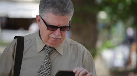 moudrý : Portrait of a cheery grey-haired man with mustashe standing and browsing the internet with his smartphone in a splendid alley in summer Dostupné videozáznamy