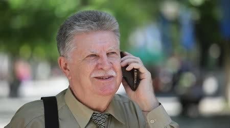 sikátorban : Portrait of a happy senior man with brave mustashe talking on phone with his friends and smiling happily in a green alley on a sunny day in summer