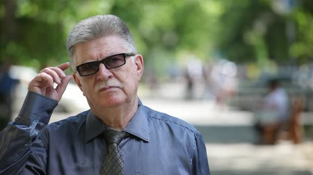 see off : Portrait of a confident old man with mustashe standing in a shirt with a necktie, smiling and taking off his sunglasses in an alley in summer Stock Footage
