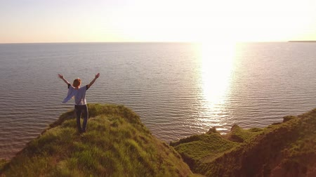 bob hairstyle : Aerial pan of a happy woman with pareo raising hands while standing on a spiky hill at the Black Sea and enjoying the golden sun path in summer Stock Footage
