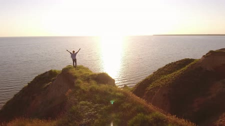 bob hairstyle : Aerial pan of a happy blond woman with pareo raising hands while standing on a sharp peak at the Black Sea and enjoying the sparkling sun path in summer Stock Footage
