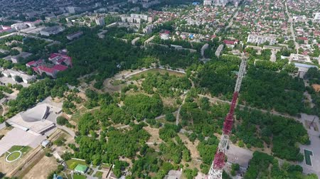 впечатляющий : An exciting bird`s eye view of a red and white television tower made of metallic lattice installed in a city green area on a sunny day
