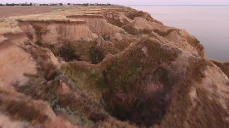 montanhoso : An exciting view from a low flying drone of a sandy mountaneous shore with narrow gorges and green patches at the Black Sea in summer