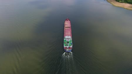 impressive skyline : An amazing bird`s eye view of a cargo barge moving slowly in the middle of the Dnipro river and leaving a white waterway in summer Stock Footage