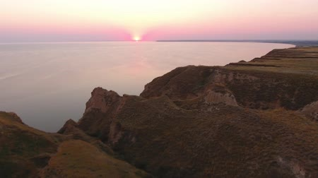 barro : A magic bird`s eye view of the shining rosy and violet sunset over the surrealistic rosy surface of the hilly Black Sea coastline in summer Stock Footage
