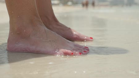 ślady stóp : A cheery closeup of female feet with red pedicure standing and relaxing on a yellow beach under warm sea waves in Dubai on a sunny day in summer Wideo