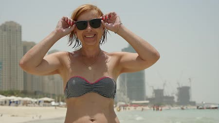 stojan : Portrait of a cheerful blond woman smiling happily and taking off her sunglasses on a sandy beach in Dubai with skyscrapers in slow motion