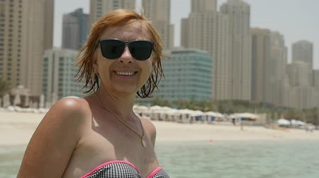 artı : Portrait of a happy blond woman in sunglasses and bikini standing on a sandy beach and smiling in Dubai with skyscrapers in the background in summer