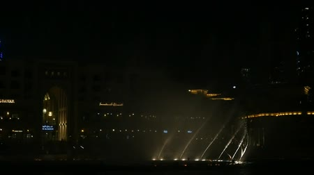 largest city : Dubai, United Arab Emirates - June 5, 2018:An impressive view of a giant fountain at Burj Khalifa with dancing waters moving in the evening in slo-mo