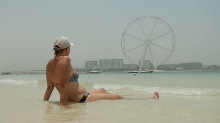 waters : A back view of a romantic woman in a white cap sitting in sea waters on shore and watching a high Ferris wheel in Dubai , slow motion