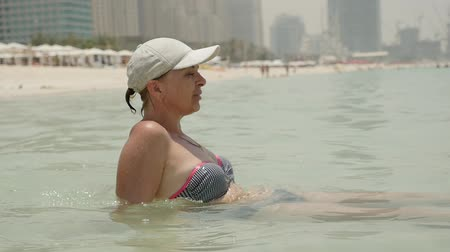 waters : Profile of a happy woman in a white cap and bikini sitting in sea waters on shore and looking at sea waves in Dubai with skyscrapers in slo-mo