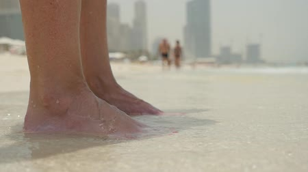 ślady stóp : An original closeup of woman`s feet with red pedicure standing on a sandy shore under moving sea waves in Dubai with skyscrapers in summer Wideo