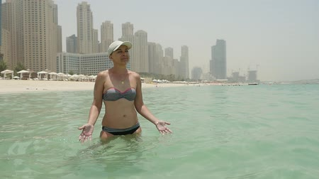 patting : Portrait of an optimistic woman in bikini, a white cap and sunglasses on it, patting sea water and standing on a sandy beach in Dubai in summer